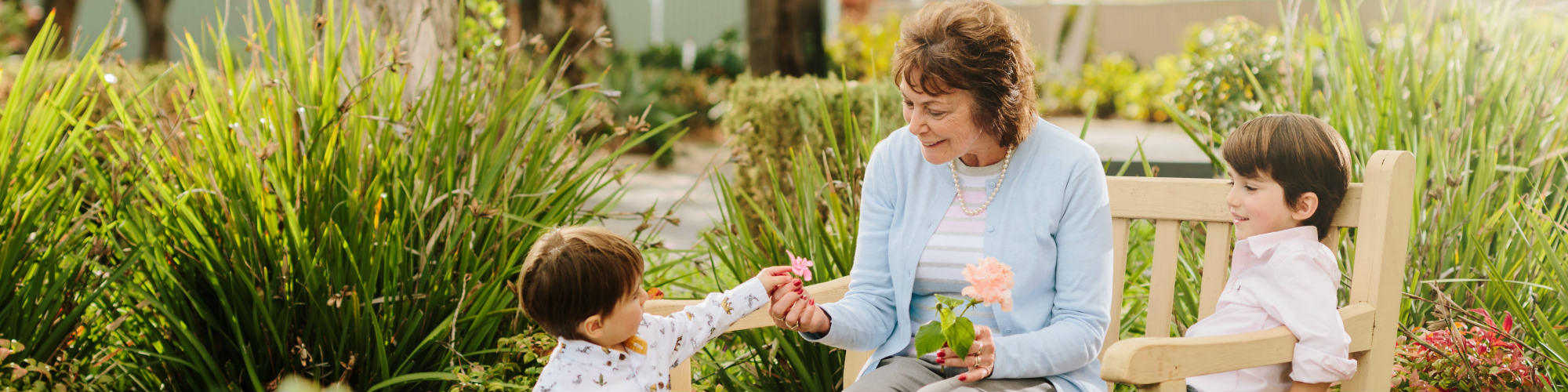 Aveo-Corporate_Lifestyle_Grandmother-with-flowers-from-grandchildren-on-bench_external_hero-2000×500